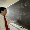 professor writing on chalkboard