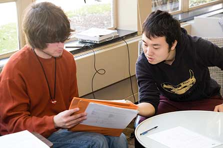 two male students looking over study notes