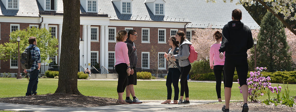 Students talking outside Monroe Hall on a sunny day