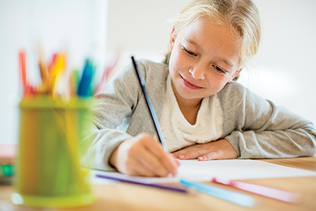 Children drawing with a colored pencil