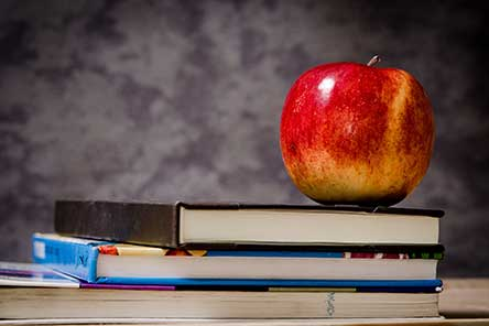 An apple on top of school textbooks