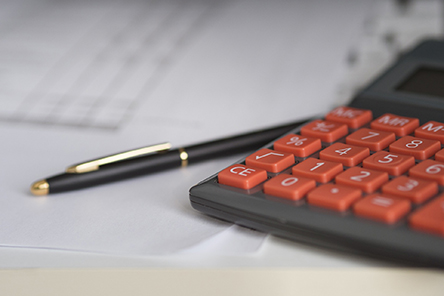 calculator and pen on top of spreadsheet