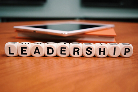 The word leadership spelled out on desk in front of books and tablet