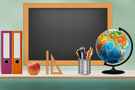 desk with globe, books and apple and blackboard in background