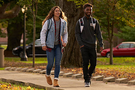 Two students walking on campus with fall foliage
