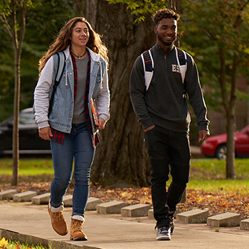 Two students walking on campus with fall foliage.