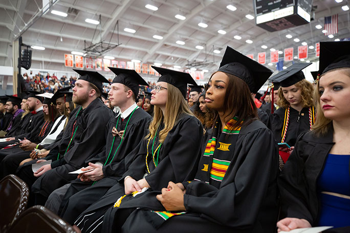 A group of students sitting at their commencement ceremony