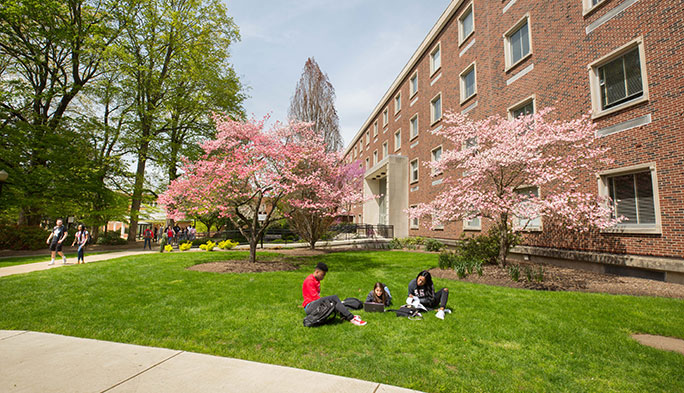 Two students sitting on lawn in front of Stroud Hall