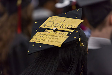 A decorated commencement cap with the word 'Believe'
