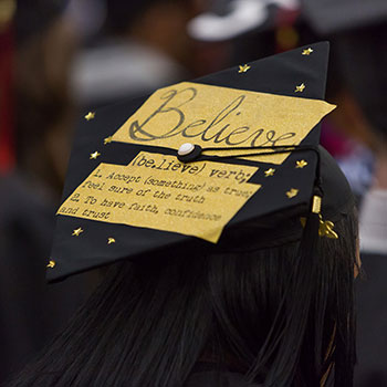 A decorated commencement cap with the word 'Believe'.