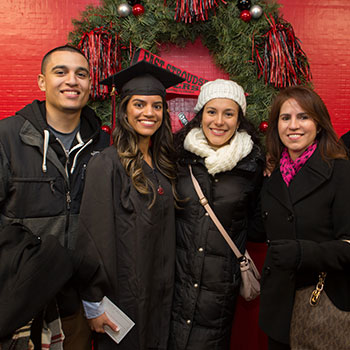 A graduating student posing with her family.