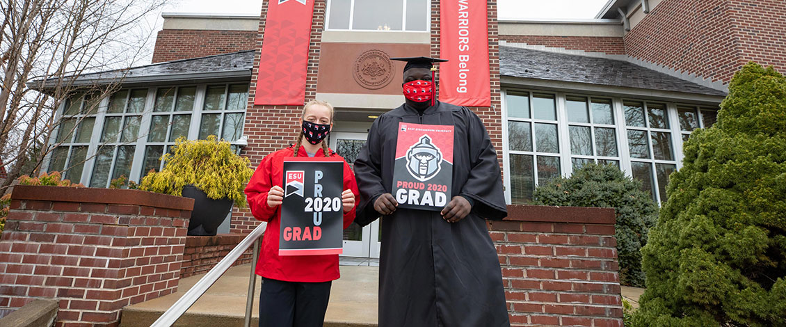 Two students wearing commencement garb in front of Reibman Administration Building