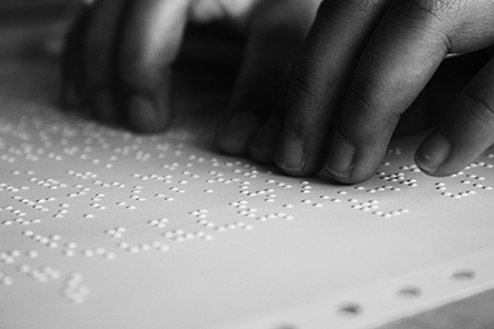 hands reading braille on a paper