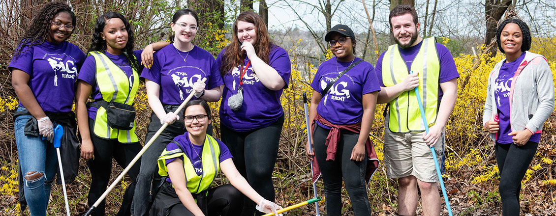 Students holding rakes during a community clean-up event