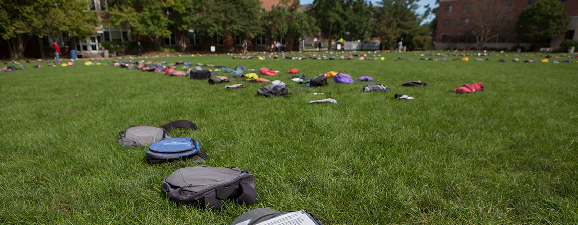 "Backpacks arranged on the grass for a ""Send Silence Packing"" event"