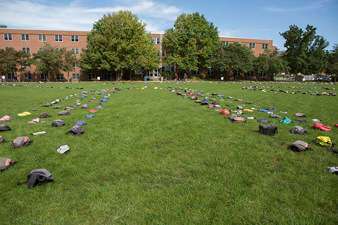 Backpacks laying on the grass as part of Send Silence Packing.