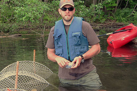 Graduate Student Larry Laubach knee deep in a lake capturing turtles