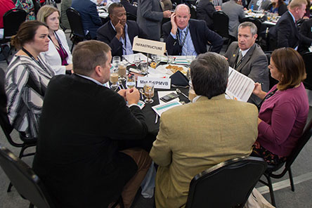Economic Outlook Summit attendees engaged in conversation around a table