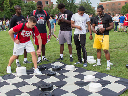 Students playing a giant checkers lawn game