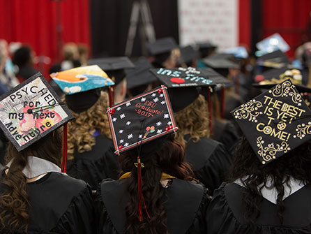 Students at commencement with decorated caps