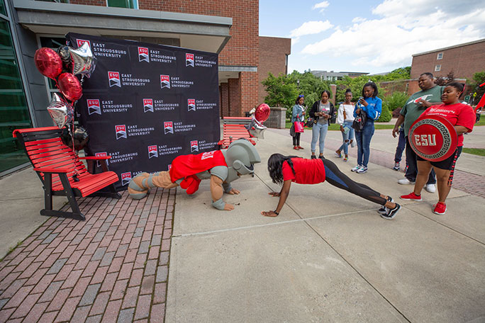 Warrior mascot doing push-ups with student during orientation