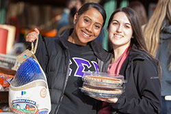 Students holding donated pies and a turkey