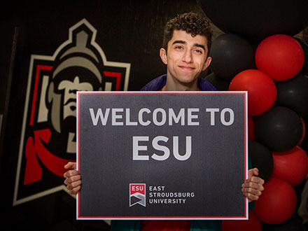 Smiling student holding up a sign stating, Welcome to ESU.