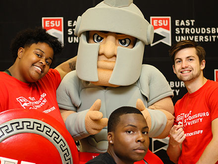 Three students posing with the Warrior mascot