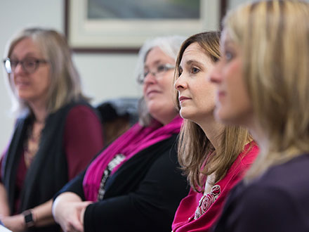 A group of female educators listening intently.