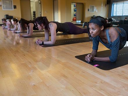 Six students in a row doing plank exercises in a workout studio