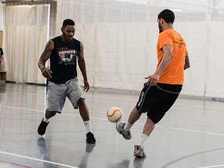 Students are playing an indoor soccer game