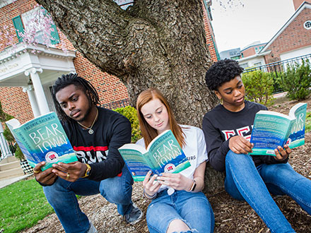 Three students sitting under a tree, reading Beartown