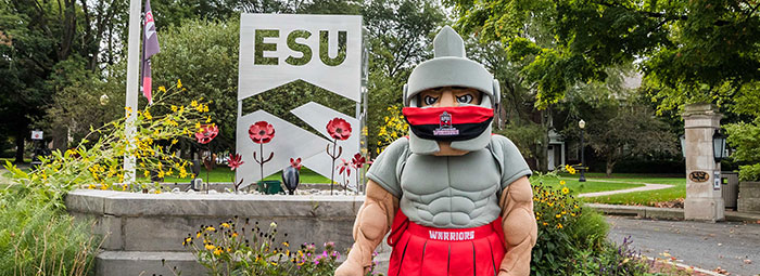 The Warrior wearing a face mask near the E.S.U. sign