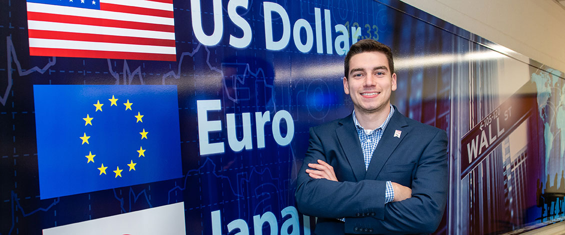 Student Michael Tomei stands in front of a backdrop showing major international currencies