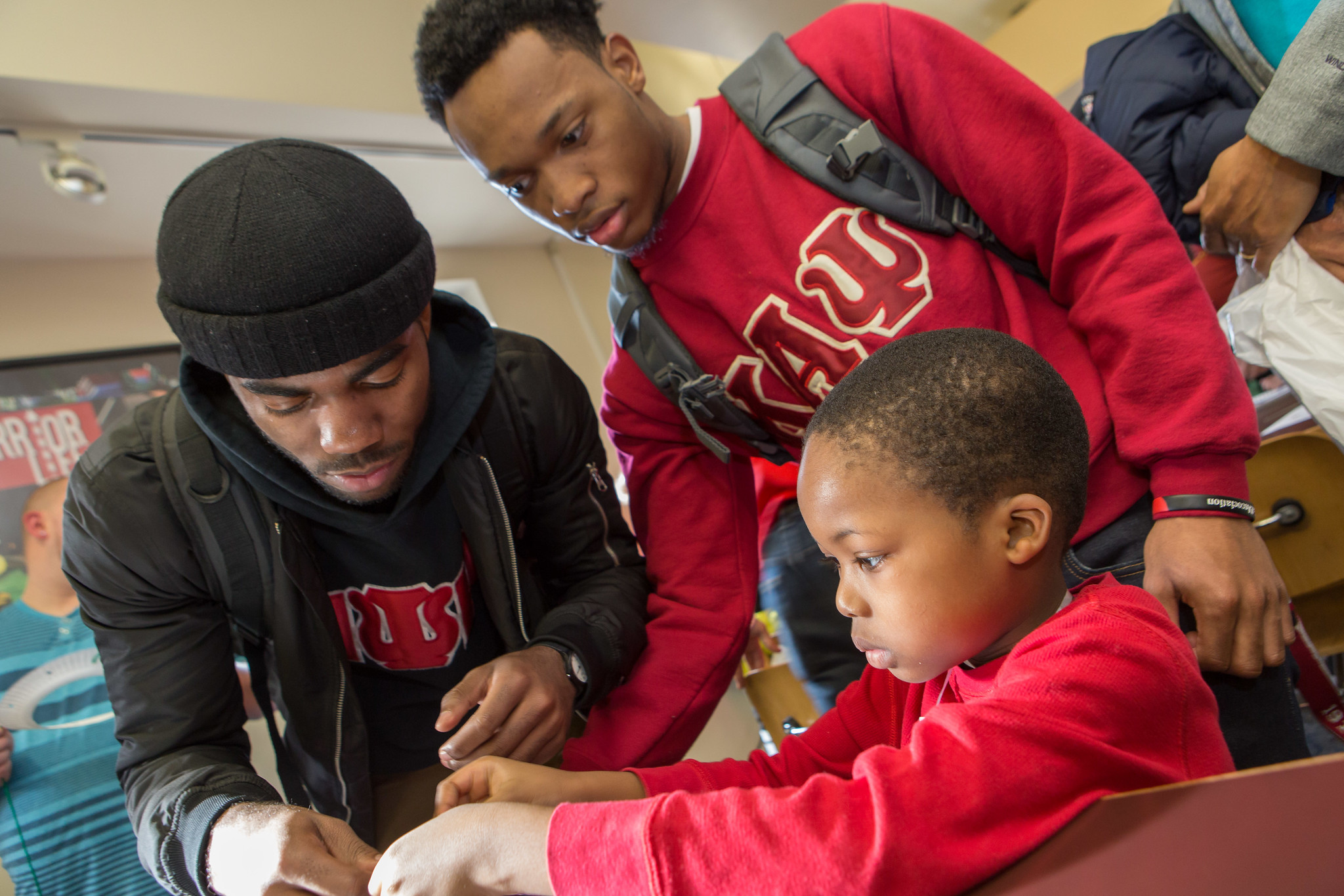 Two ESU fraternity students helping an young child