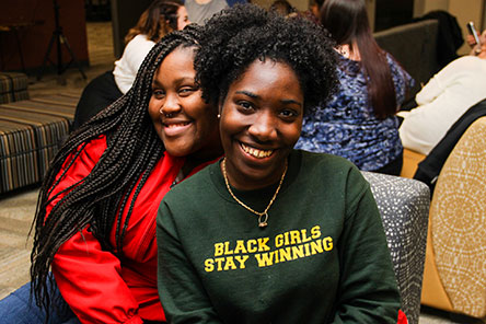 Two students of color smiling, one with a shirt reading Black Girls Stay Winning