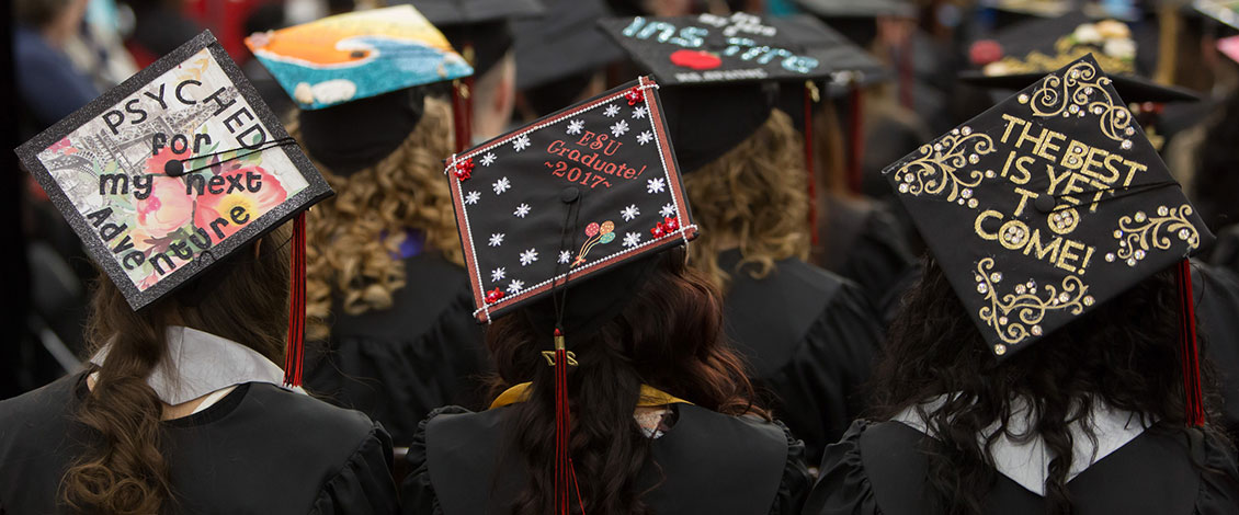 Students wearing decorated caps at commencement