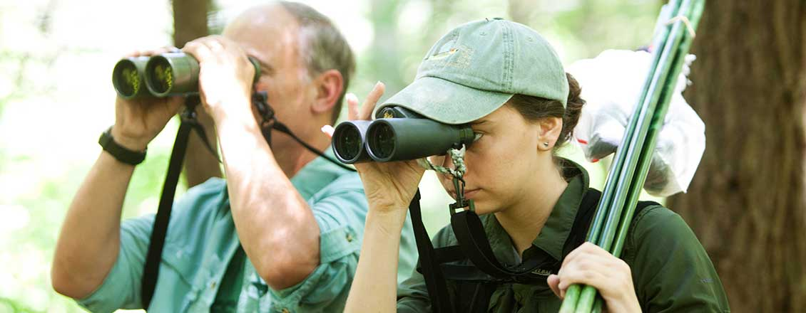 Teacher and student looking for birds using binoculars