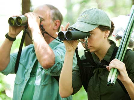 Teacher and student looking for birds with binoculars