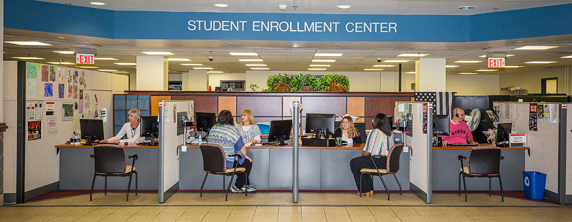 Enrollment Center front desk, students being assisted