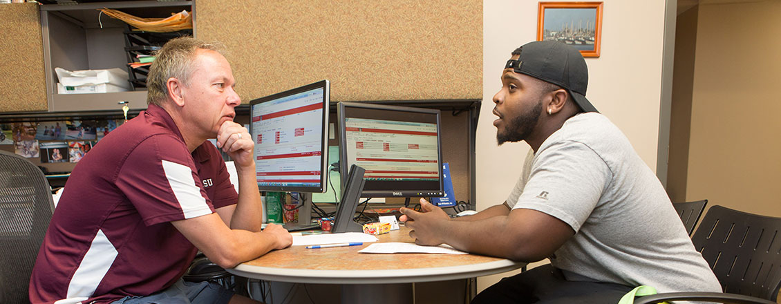 A student talking with a faculty member during an advising session