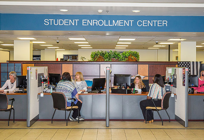 Students speaking with staff in the Student Enrollment Center lobby