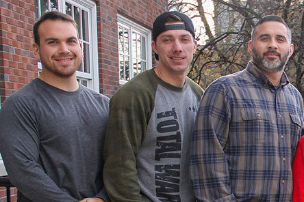 Three well-built male students standing together