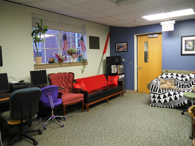 The Veterans Center room showing two couches, several chairs, and American flags